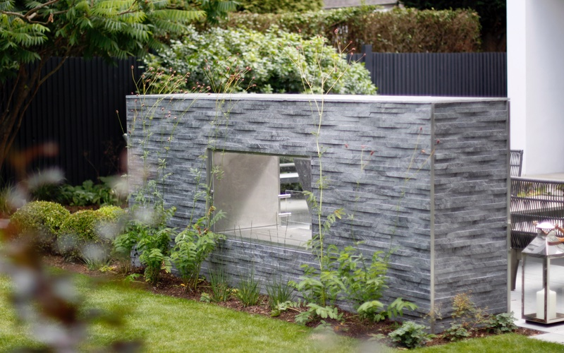 Textured cladding on fireplace, south west London garden.